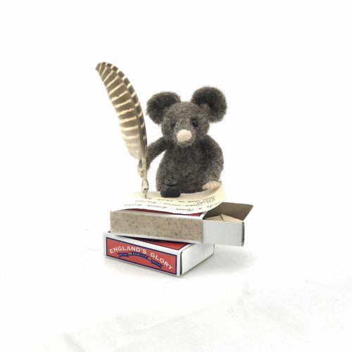 a card design of a needle-felted mouse writing with a feather quill at a table made from a matchbox